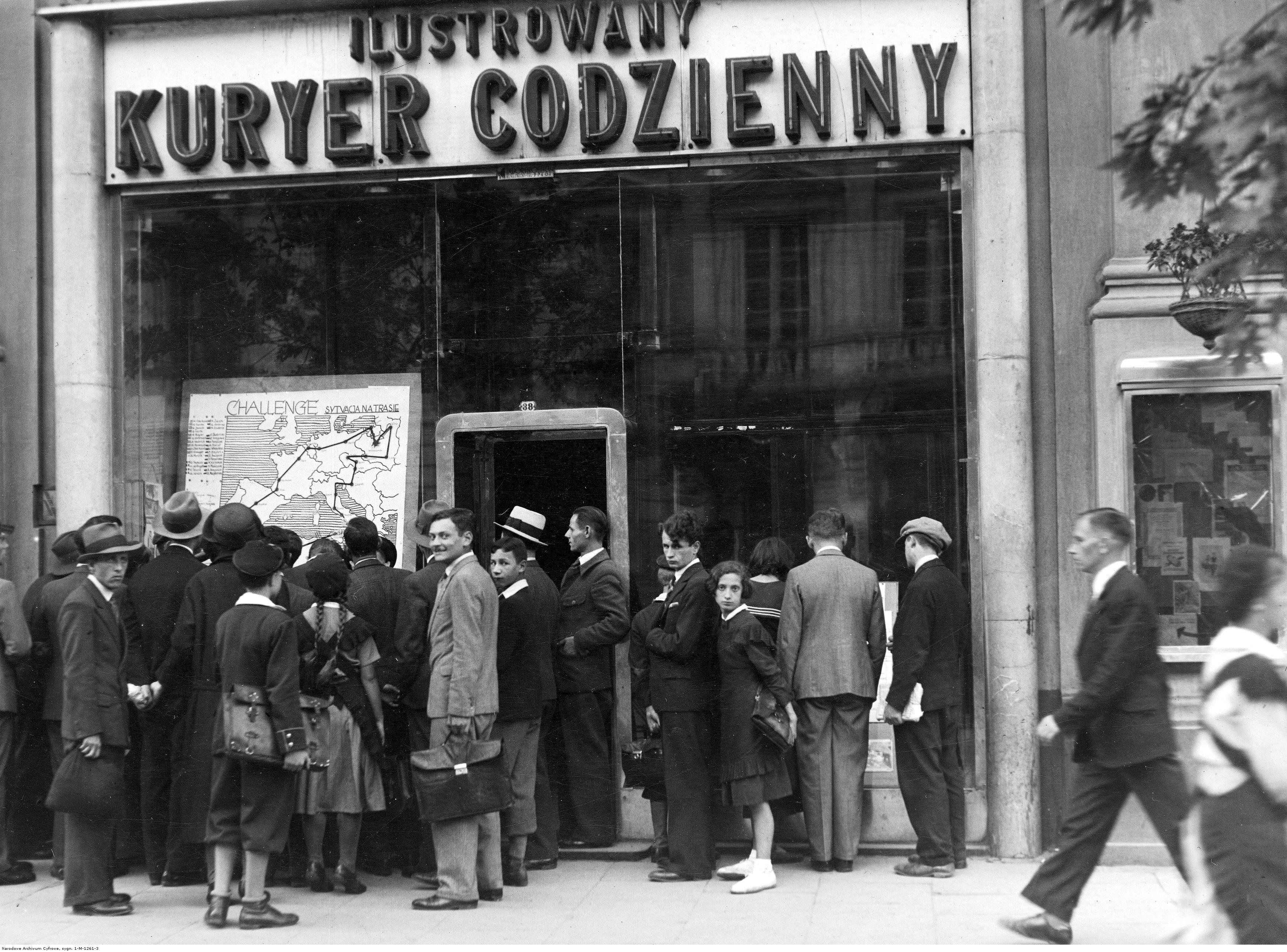 Grupa osób przed tablicą wyników Międzynarodowych Zawodów Samolotów Turystycznych (Challenge 1934) wystawioną w oknie warszawskiego oddziału Ilustrowanego Kuriera Codziennego. Fot. NAC