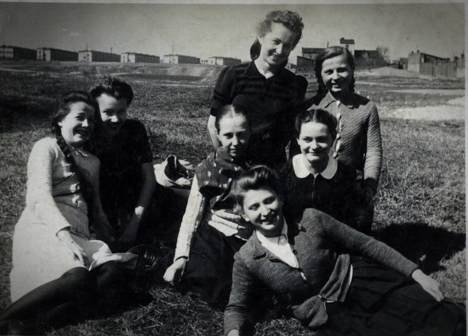 Na zdjęciu Henryka Białecka (pierwsza z lewej) i jej znajomi: obok Zofia Sierczyńska, pośrodku Krystyna Zielińska, obok niej Hanna Jankowska, z przodu Wacława Herman, z tyłu od lewej Maria Pałka i Krystyna Herman. Park Moczydło, lato 1939. W tle osiedle przy Obozowej, jako pierwsze zbombardowane we wrześniu 1939. Fot. zbiory Henryki Białeckiej/AHM