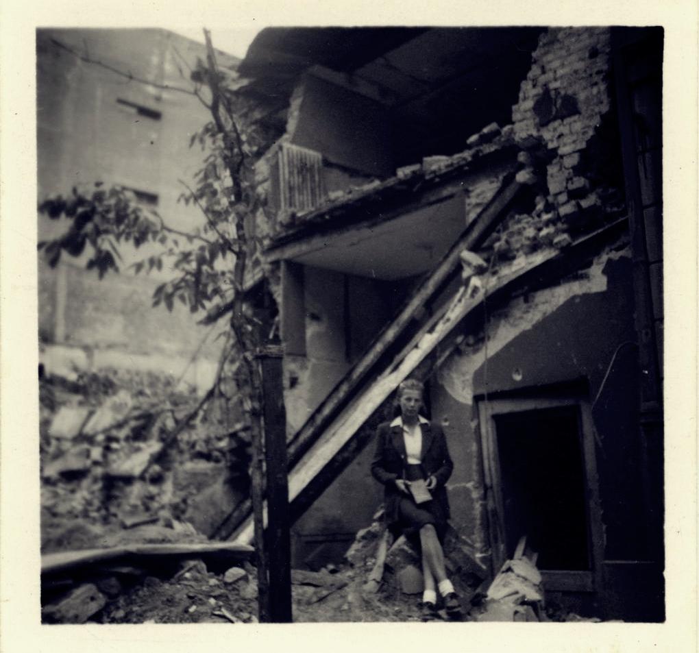 """Anna Mizikowska przy ruinach kamienicy """"Pod Husarzem"""", ulica Marszałkowska 74/Hoża 31. 1945. Fot. zbiory Anny Mizikowskiej/AHM"""