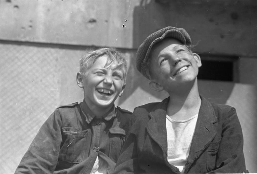 Warszawa, 1946-07-01. Najm³odsi mieszkañcy stolicy spêdzaj¹ wiêkszoœæ czasu wœród ruin zniszczonych domów i podwórek. Nz. dwaj ch³opcy pozuj¹ do zdjêcia, uœmiechniêci mimo trudów powojennego ¿ycia. ms PAP/Jerzy Baranowski   Warsaw, July 1, 1946. Warsaw's youngest spend most of their time among ruined buildings and backyards. Pictured: two boys smile despite the hardships of post-war life. ms PAP/Jerzy Baranowski